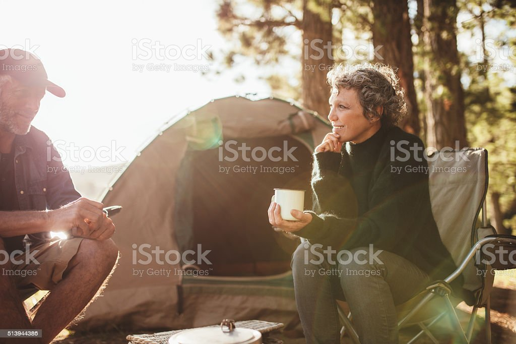 Relaxed couple sitting outside tent while camping nearby lakeside stock photo
