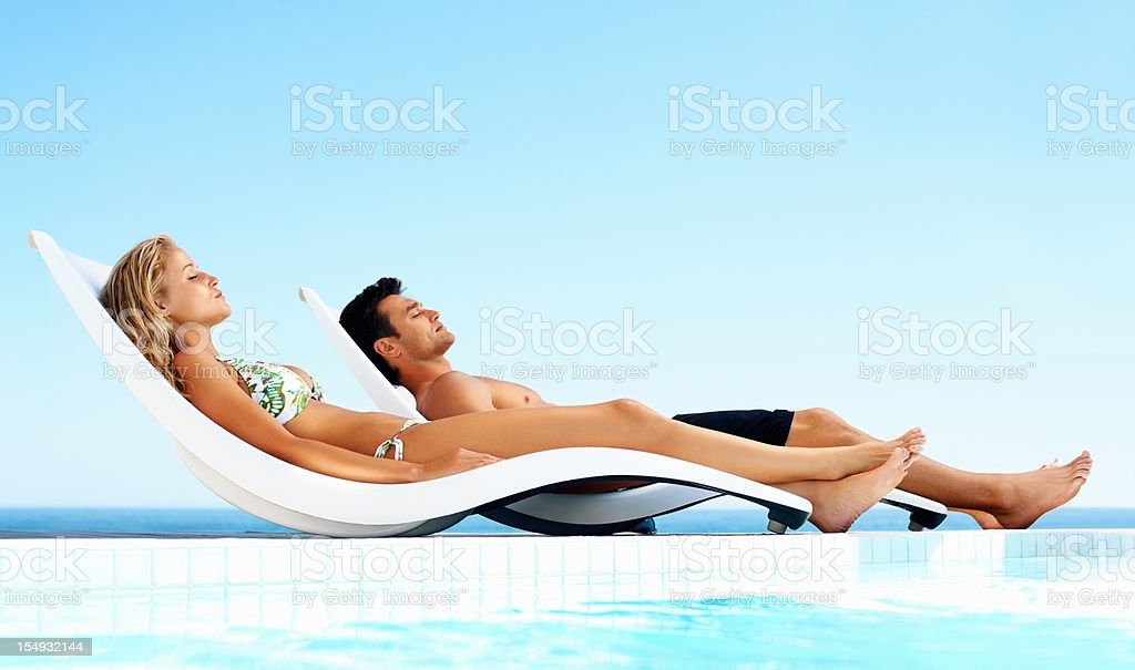 Relaxed couple sunbathing by swimming pool royalty-free stock photo