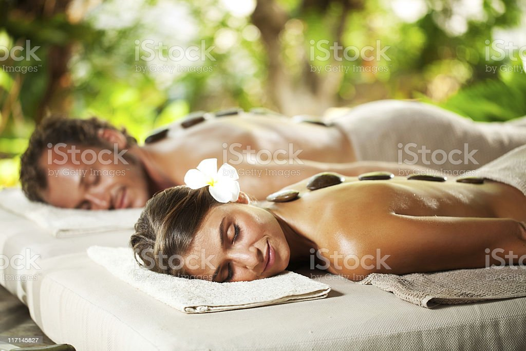 Relaxed couple with eyes closed receiving hot stone therapy stock photo