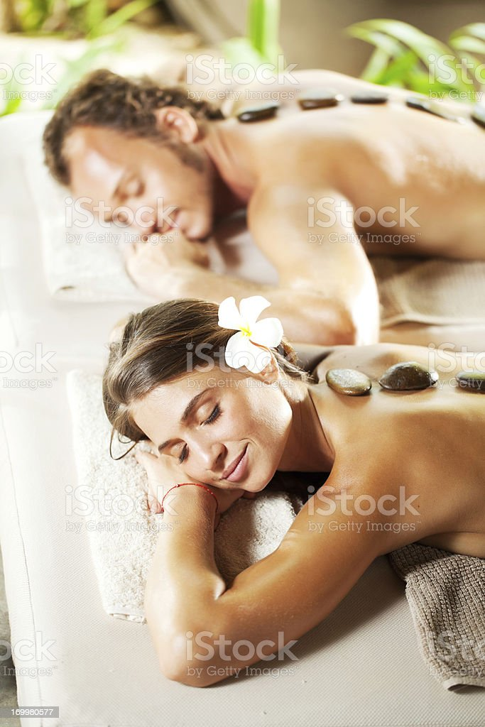 Relaxed couple with eyes closed receiving hot stone therapy. royalty-free stock photo