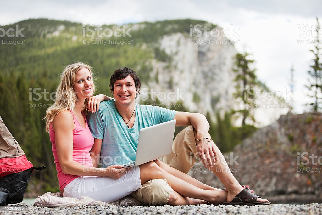 Relaxed couple with laptop while camping royalty-free stock photo