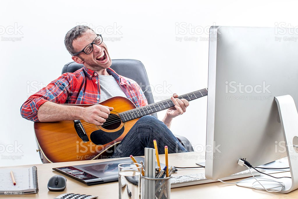 relaxed entrepreneur singing and playing guitar at home-office desk stock photo