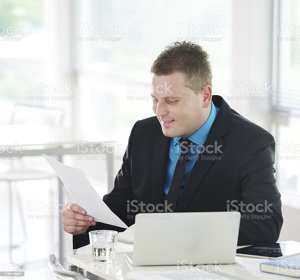 Relaxed executive sitting on desk in office reading report royalty-free stock photo
