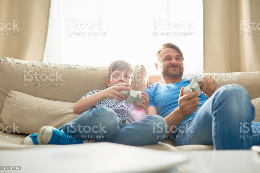Relaxed father and son on sofa stock photo