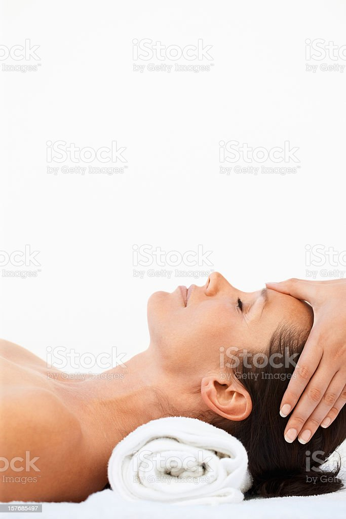 Relaxed female receiving head massage against white royalty-free stock photo