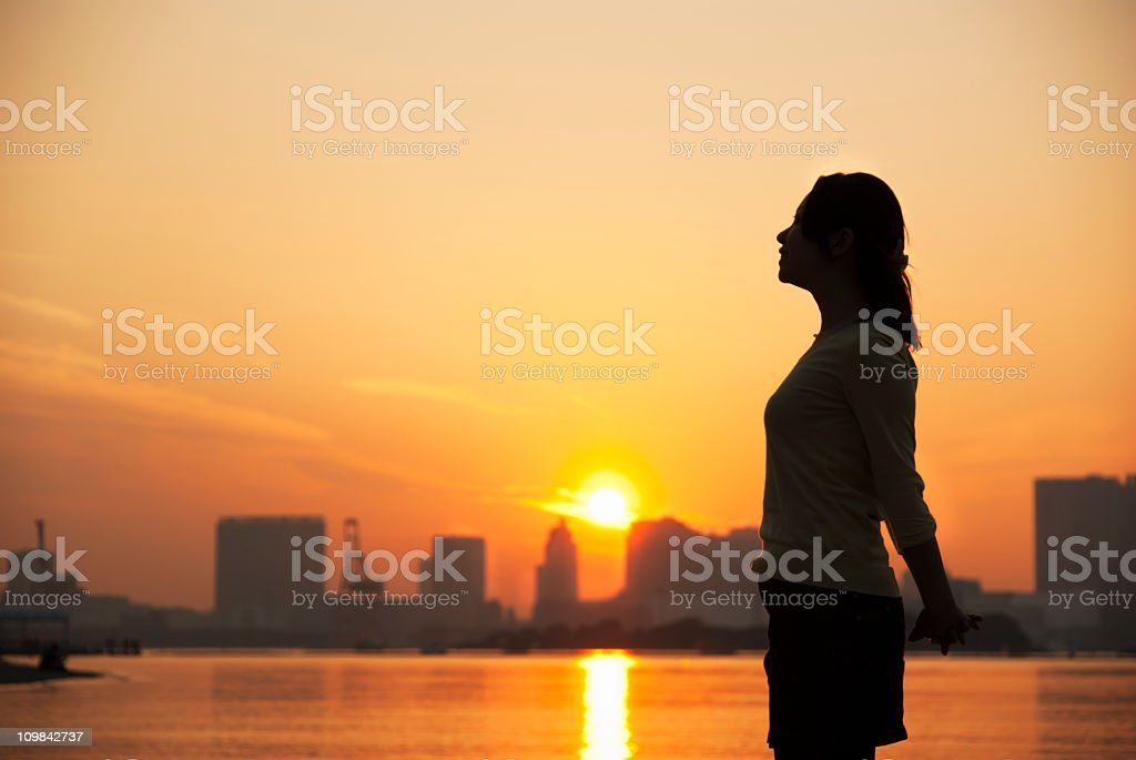 Relaxed female silhouette at Sunset in Odaiba Beach, Tokyo stock photo