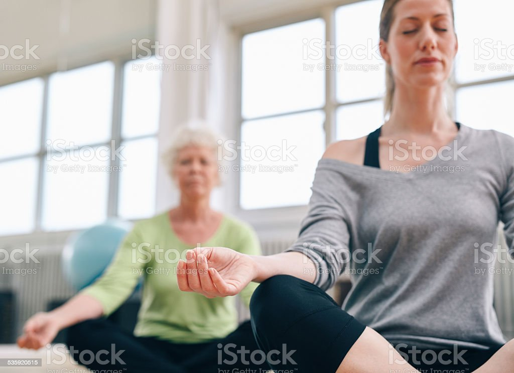 Relaxed fitness women practicing yoga at gym stock photo