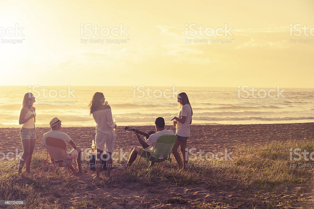 Relaxed friends beach party at sunset stock photo