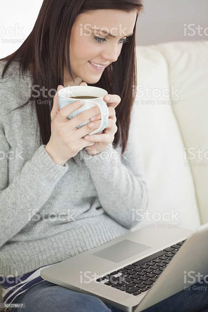 Relaxed girl sitting on sofa holding a cup of coffee royalty-free stock photo