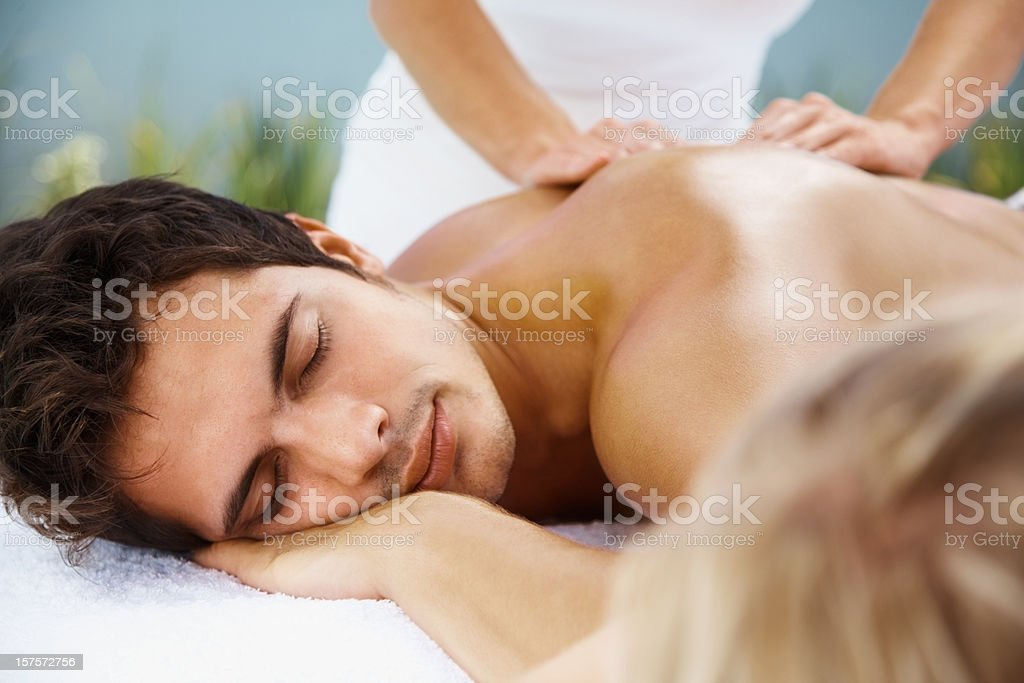 Relaxed handsome man receiving back massage royalty-free stock photo