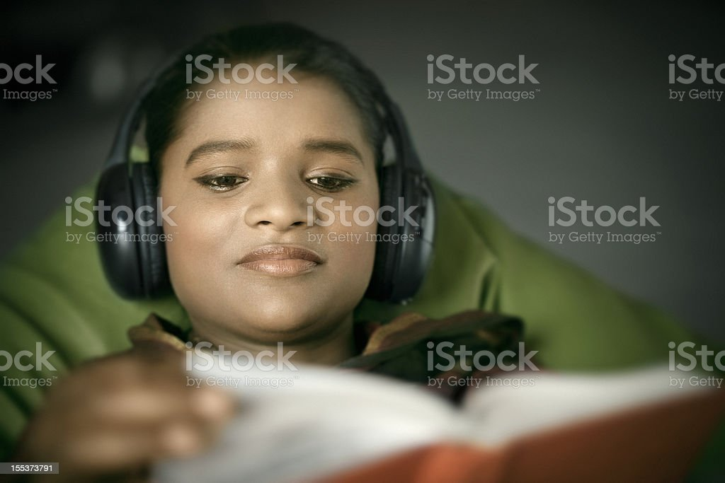 Relaxed Indian woman listening music while reading book royalty-free stock photo