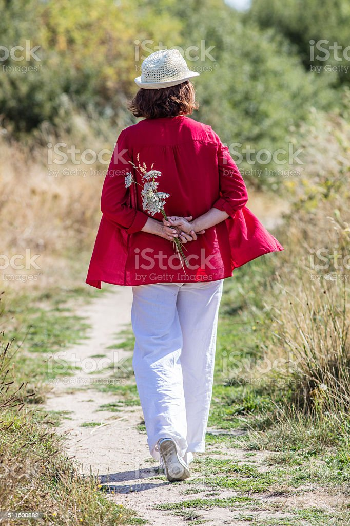 relaxed lady strolling around alone with field flowers in back stock photo