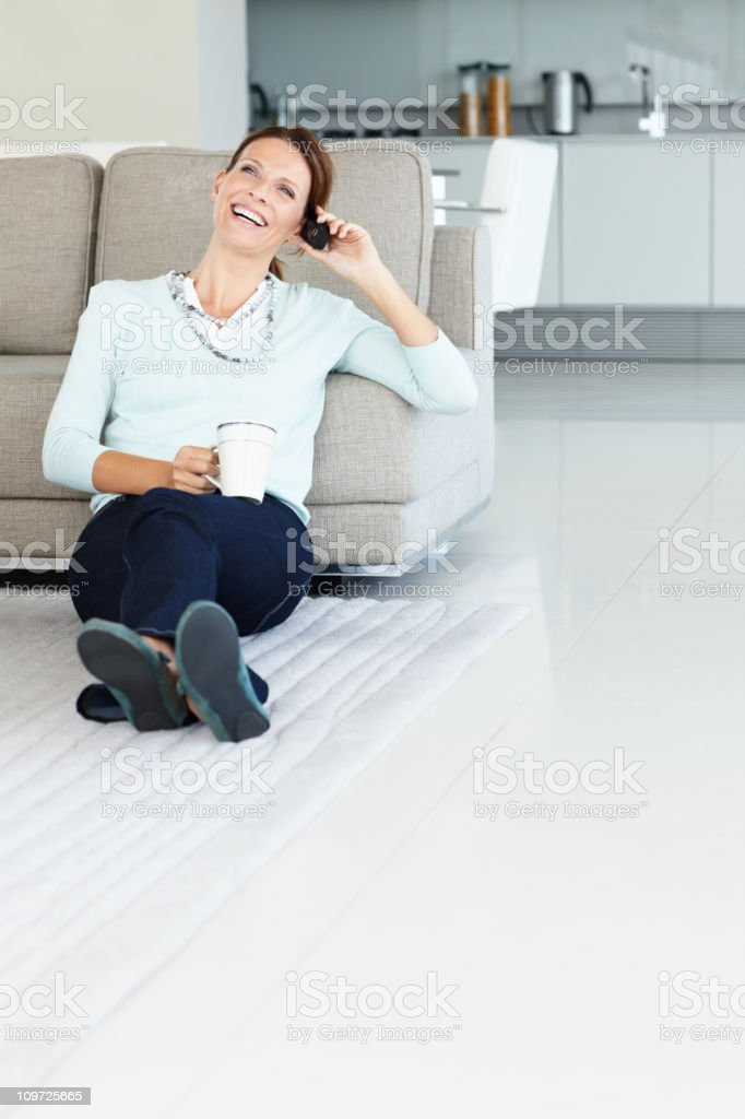Relaxed lady using cellphone while having coffee at home royalty-free stock photo
