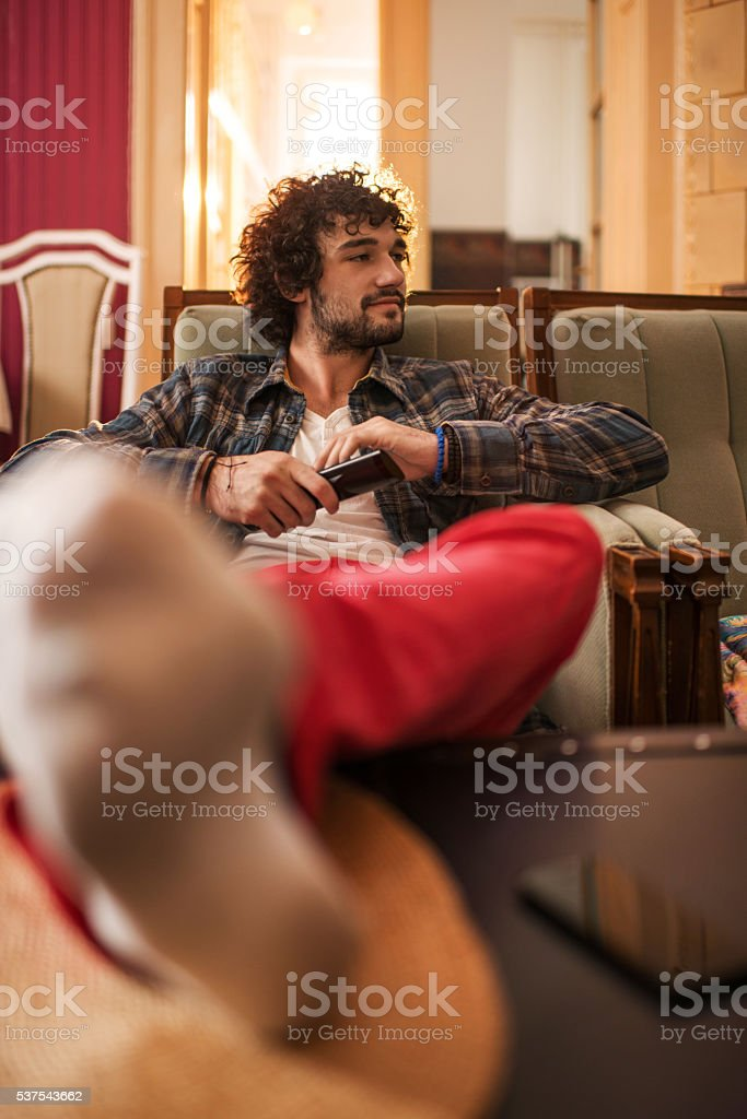 Relaxed man changing channels with remote control. stock photo