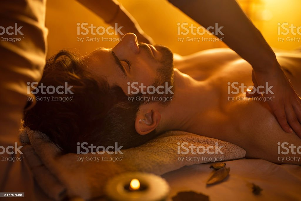Relaxed man during shoulder massage at the spa. stock photo