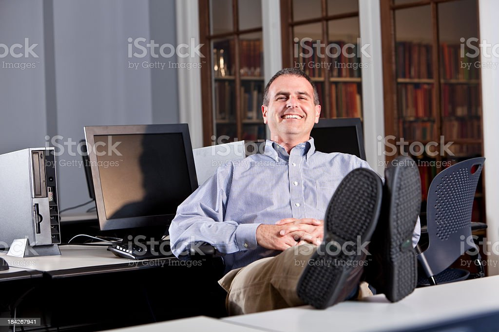 Relaxed man in office with feet up on desk stock photo