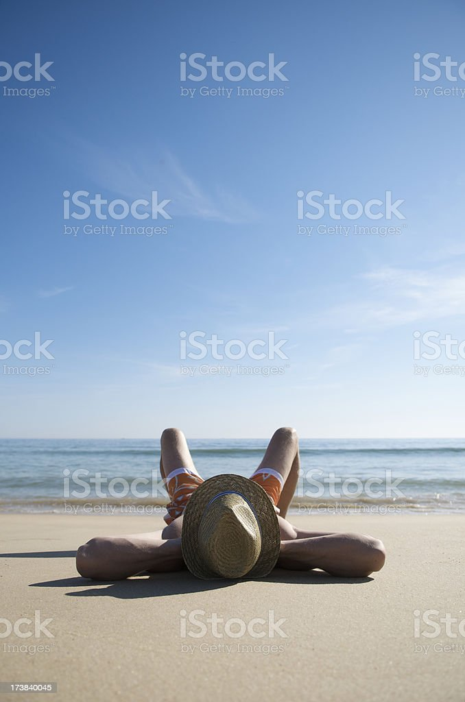 Relaxed Man in Sun Hat Reclining on Calm Beach royalty-free stock photo
