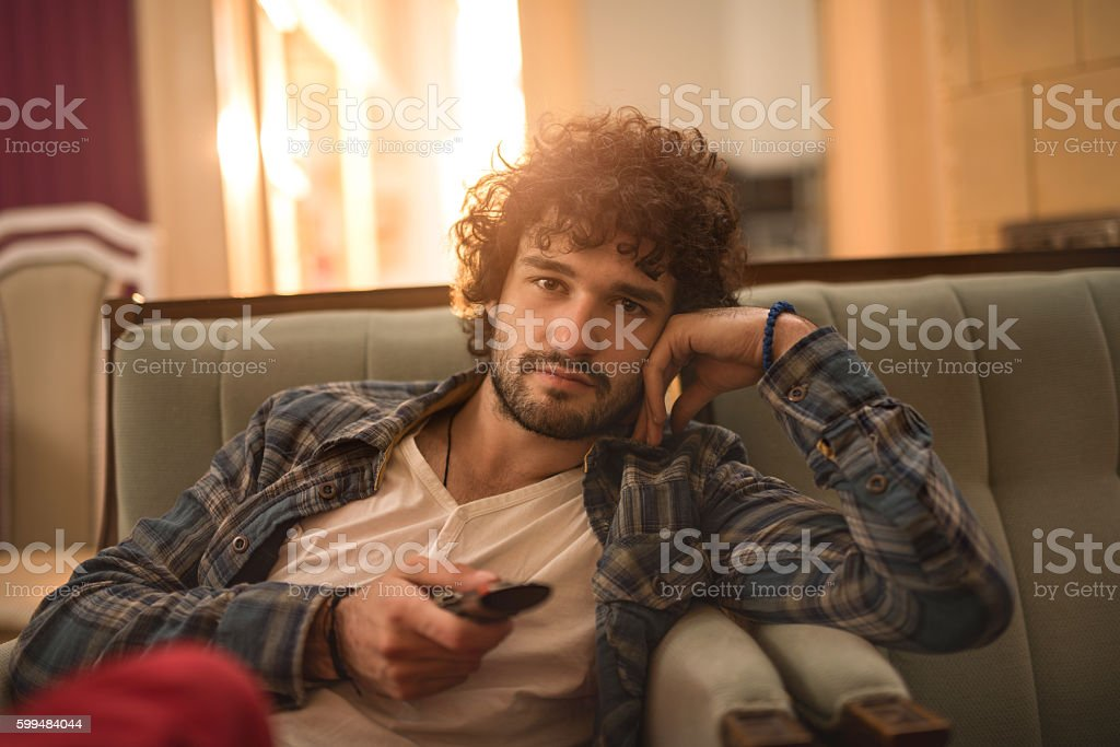 Relaxed man watching TV and changing channels with remote control. stock photo