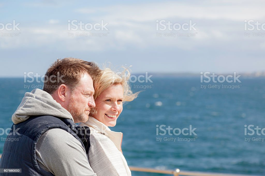 Relaxed, mature adult couple embracing and looking out to sea stock photo