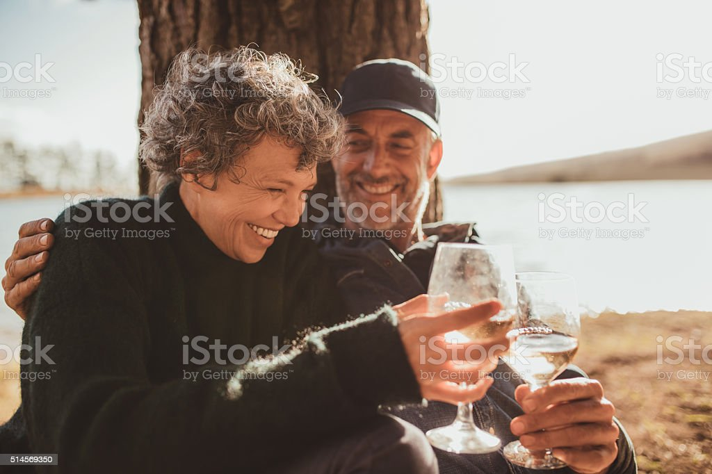 Relaxed mature couple having a glass of wine at campsite stock photo
