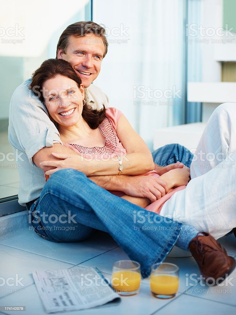 Relaxed mature couple sitting with juice glasses stock photo