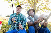Relaxed mature fishermen enjoy fishing together