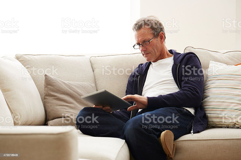 Relaxed mature man using digital tablet at home stock photo