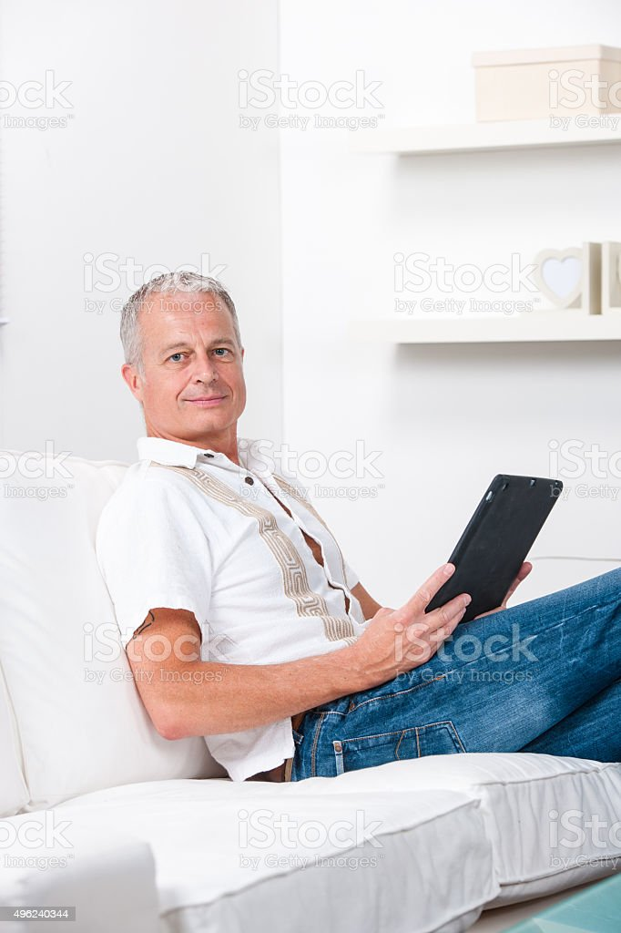 Relaxed Mature Man Using Digital Tablet In The Living Room stock photo