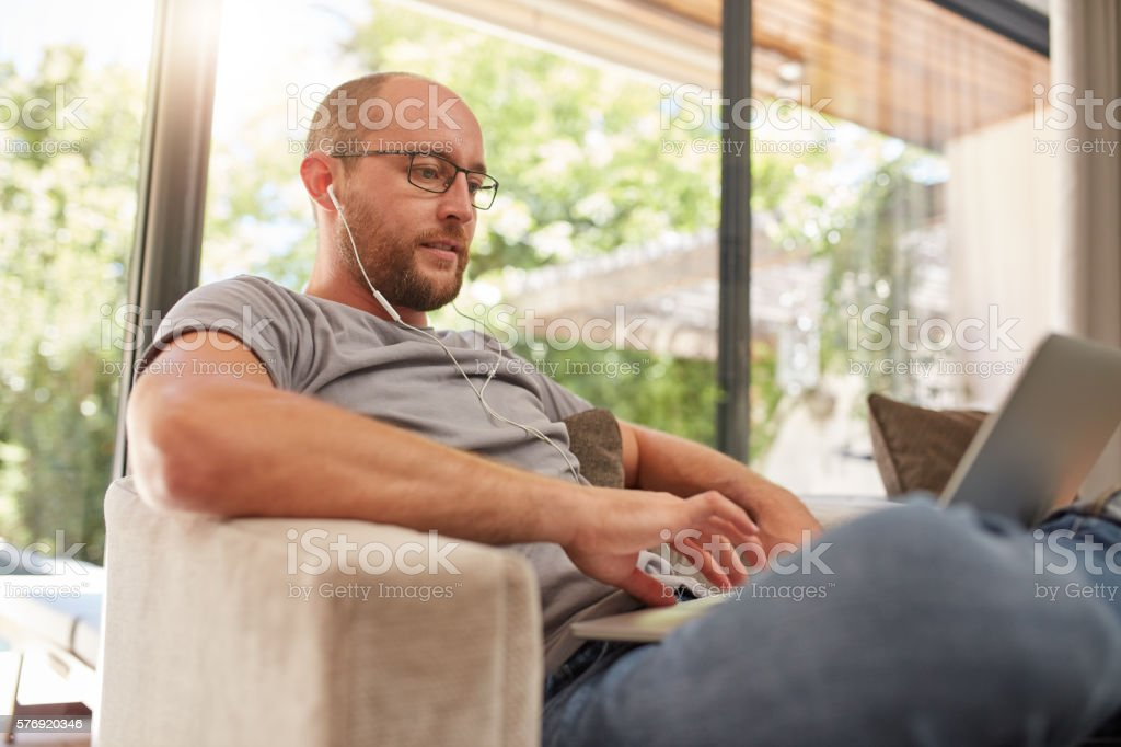 Relaxed mature man using laptop at home stock photo