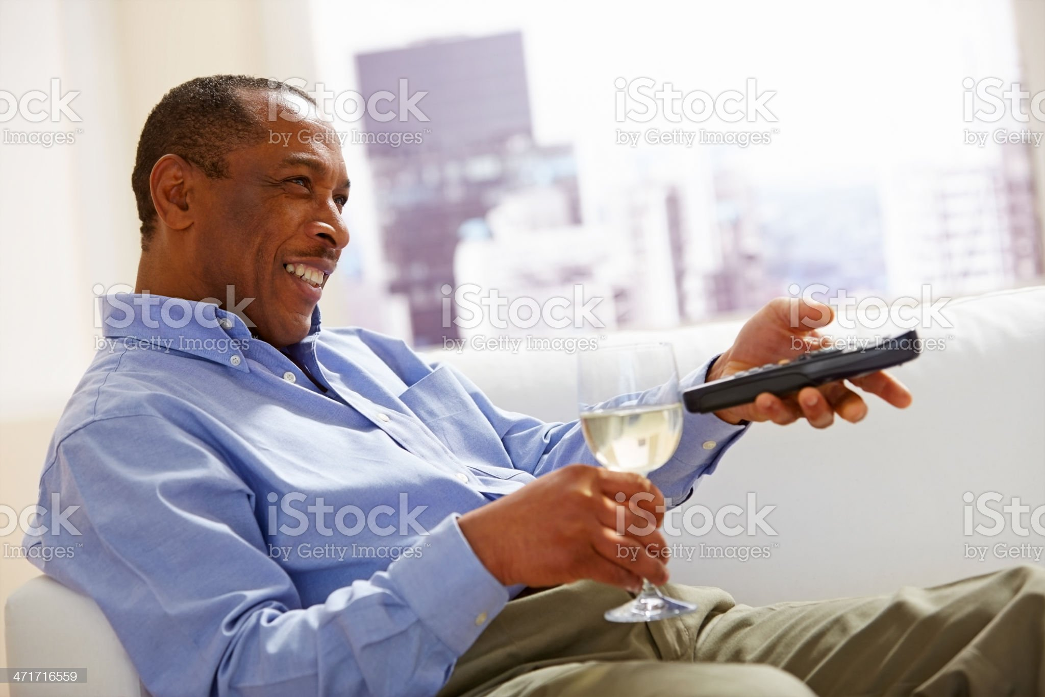 Relaxed mature man watching television with a glass of wine royalty-free stock photo