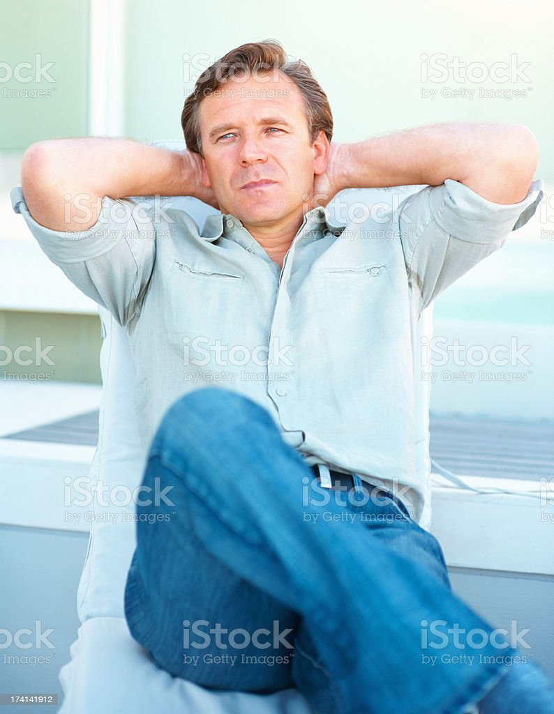 Relaxed mature man with hands behind head stock photo