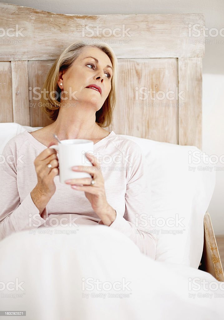 Relaxed mature woman holding coffee mug in bed royalty-free stock photo