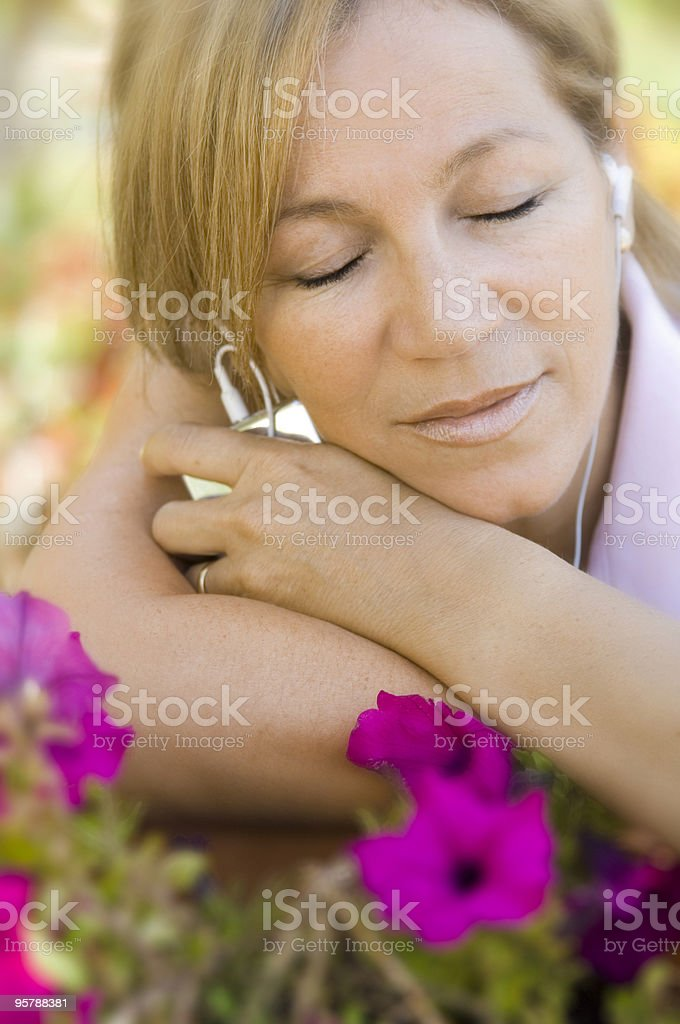 Relaxed mature woman listening music in park stock photo