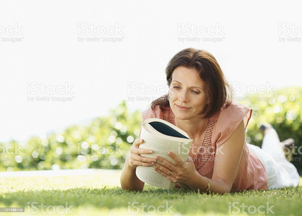 Relaxed mature woman reading a book at the lawn royalty-free stock photo