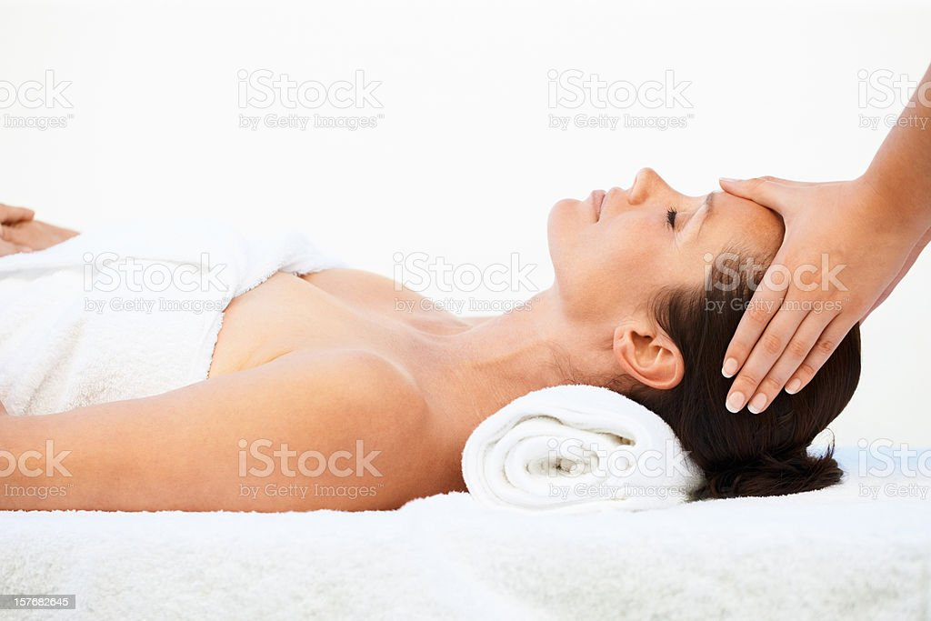 Relaxed mid adult woman receiving head massage on white royalty-free stock photo