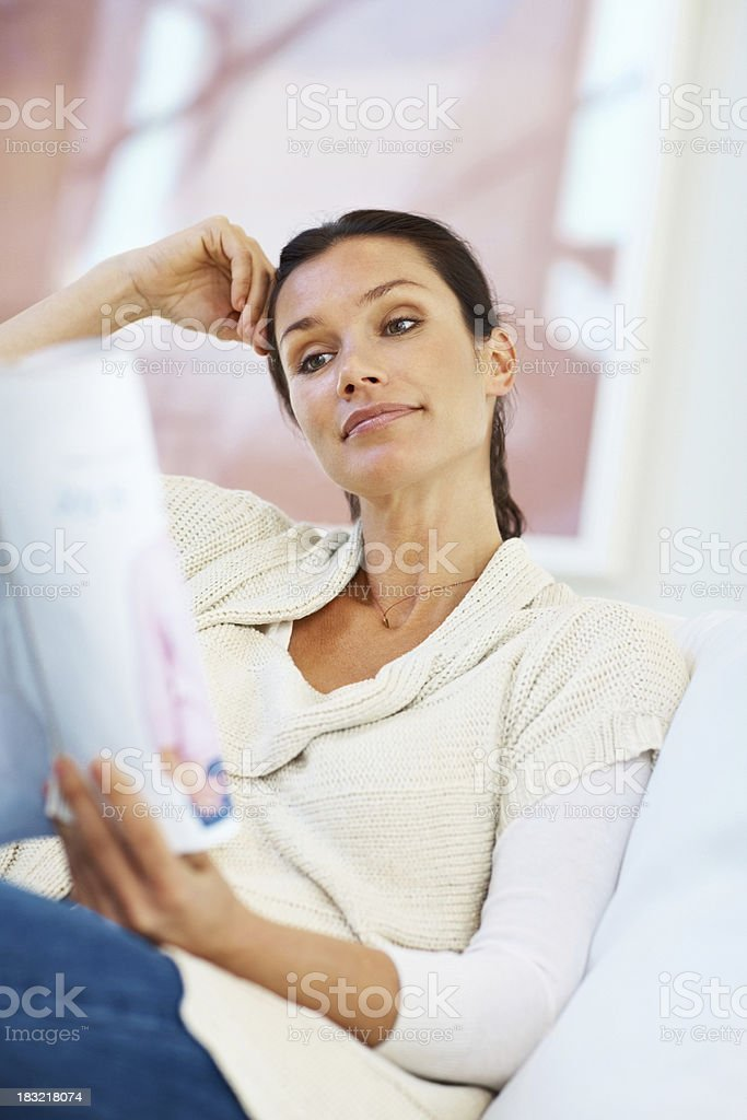 Relaxed middle aged woman reading magazine royalty-free stock photo