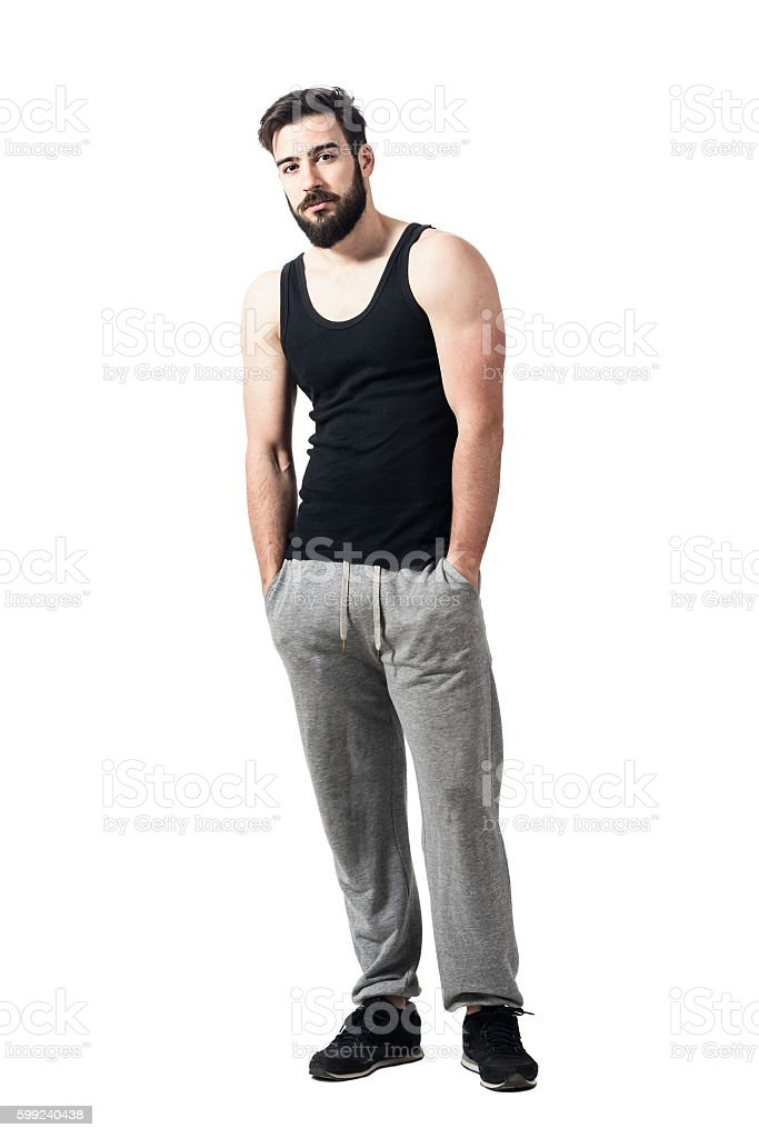 Relaxed muscular athlete with hands in pockets looking at camera. stock photo