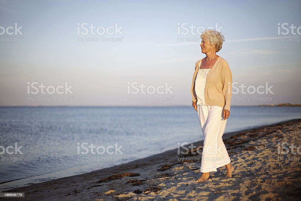 Relaxed old lady strolling on the beach stock photo