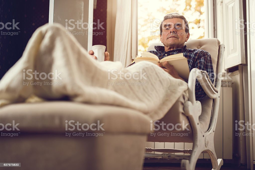 Relaxed old man reading a book at home. stock photo