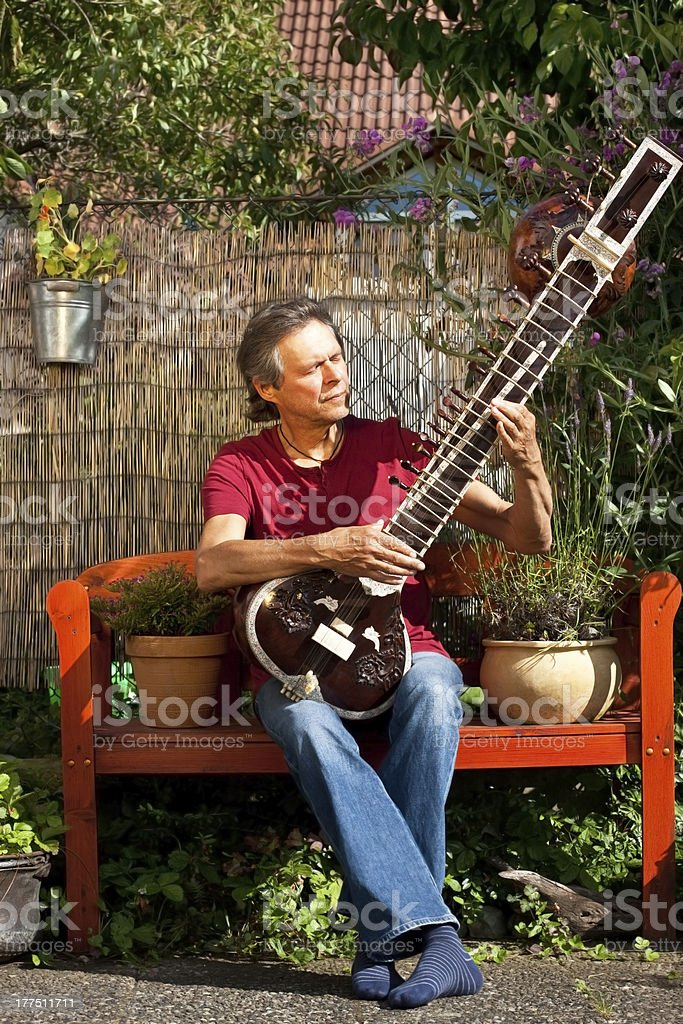 Relaxed older man is playing a sitar stock photo