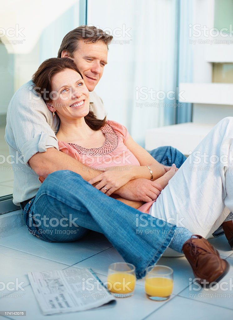 Relaxed romantic mature couple sitting with juice glasses stock photo