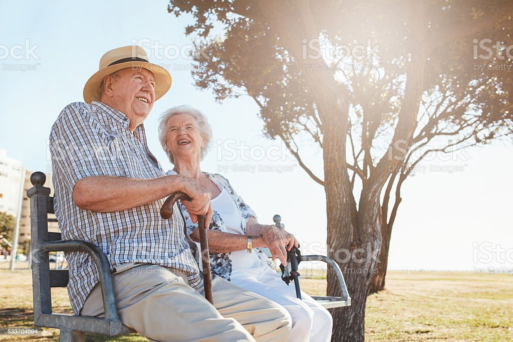 Relaxed senior couple sitting on a park bench stock photo