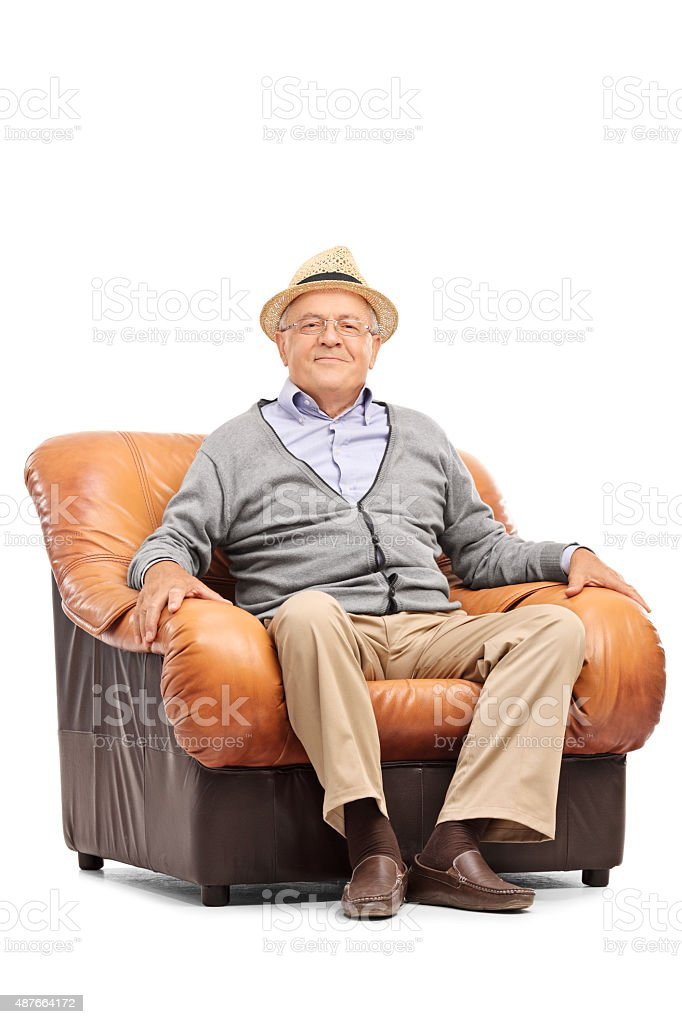 Relaxed senior gentleman sitting in an armchair stock photo