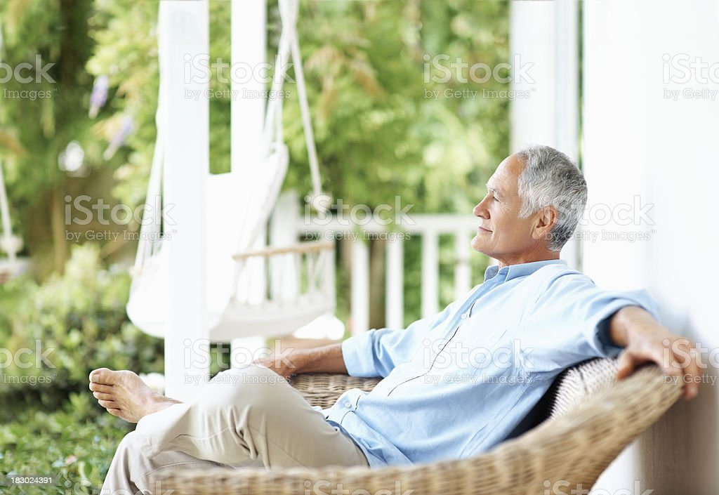 Relaxed senior man sitting on a wicker chair at porch stock photo
