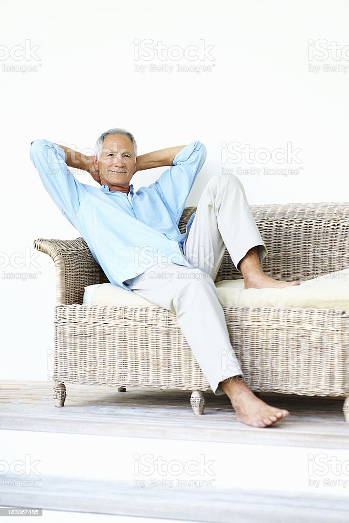 Relaxed senior man sitting on sofa with hands behind head stock photo