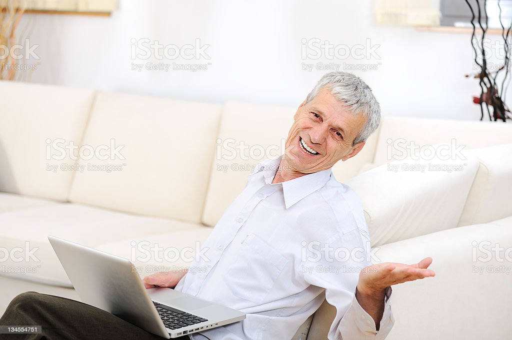 Relaxed senior man with laptop on sofa smiling royalty-free stock photo