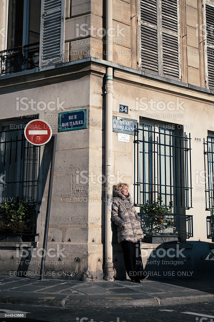 Relaxed senior woman stand against the wall to enjoy the sunshine stock photo