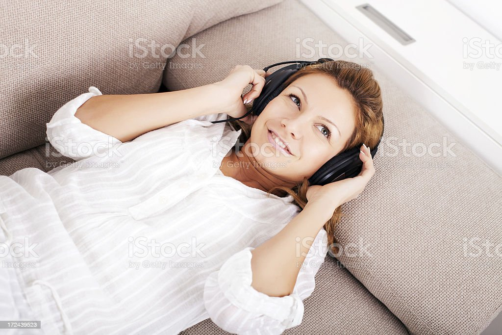 Relaxed smiling woman lying on sofa and listening music. royalty-free stock photo