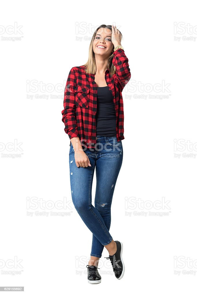 Relaxed spontaneous young casual girl laughing and touching hair stock photo