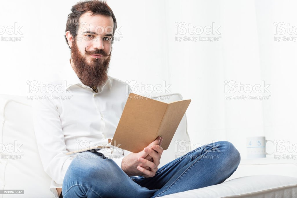 relaxed student reading in his living room stock photo